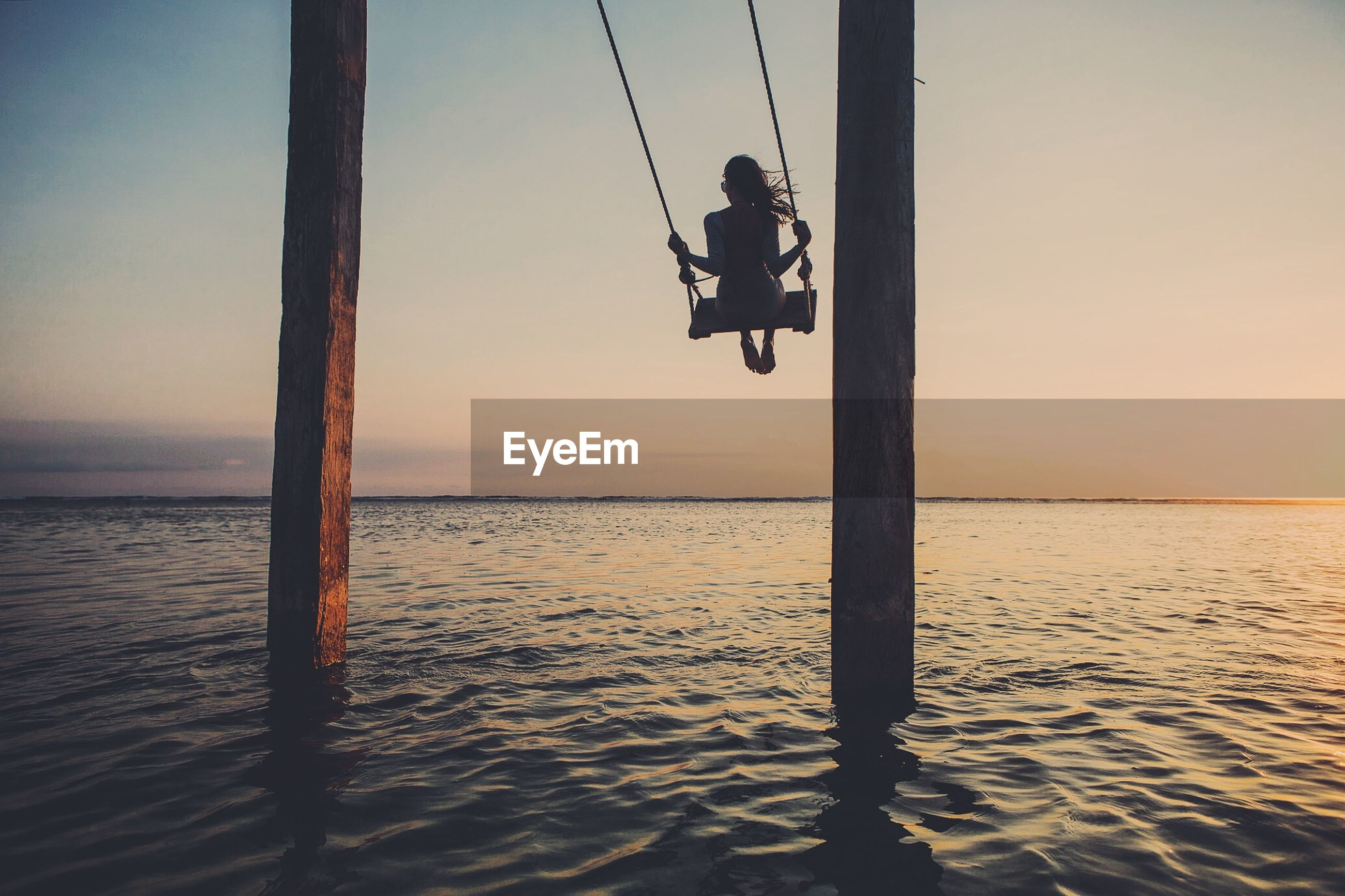 Rear view of woman on swing at sea against sky during sunset