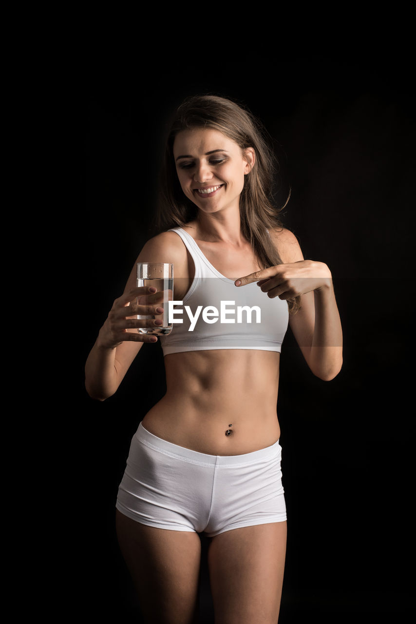 three quarter length, front view, one person, young adult, standing, smiling, studio shot, young women, indoors, clothing, beautiful woman, food and drink, beauty, refreshment, lifestyles, women, drink, looking at camera, black background, hair, hairstyle, glass
