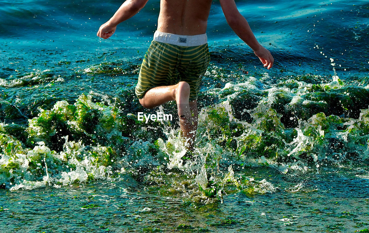 Low section of shirtless man running in sea