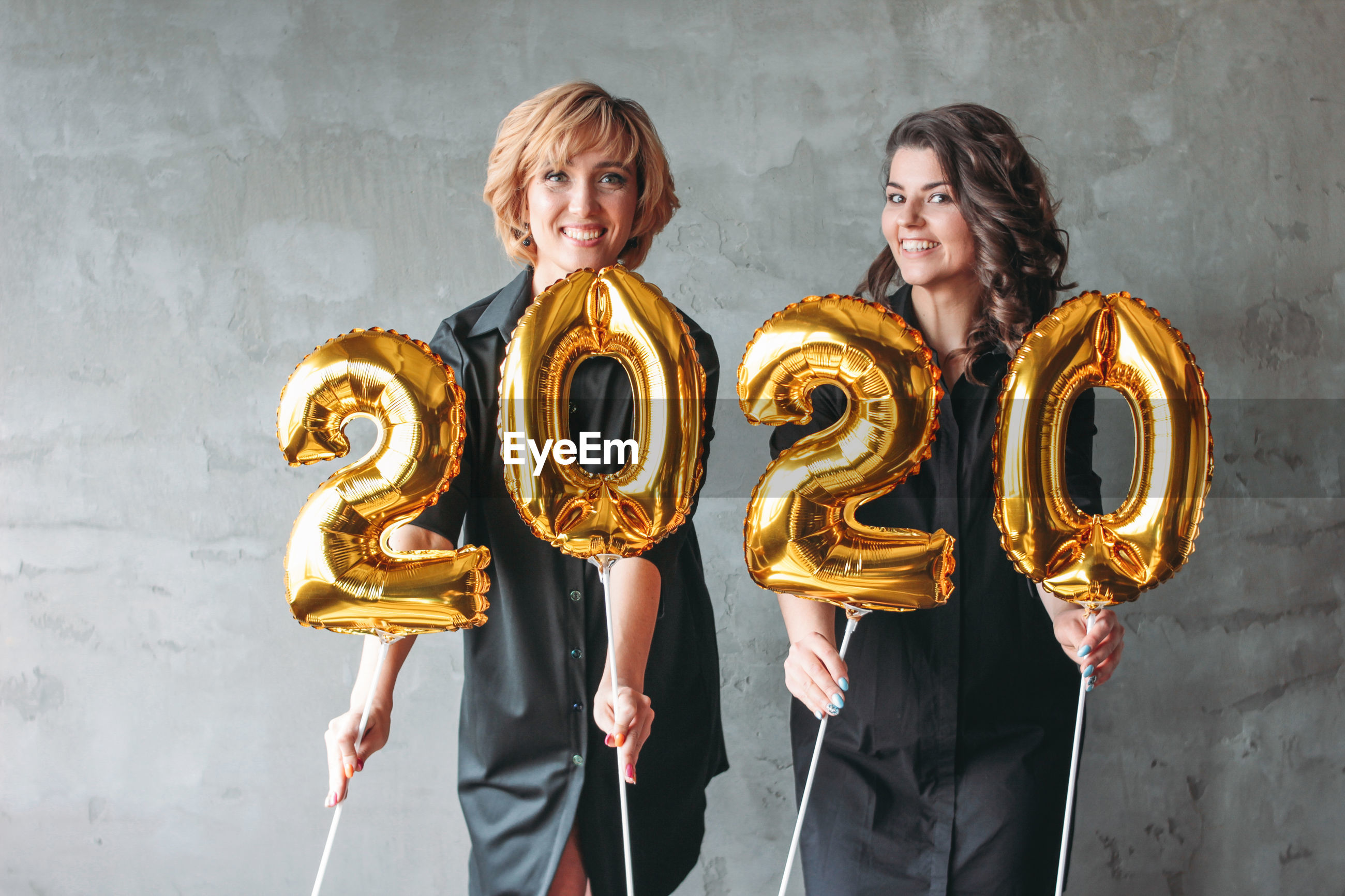 Portrait of smiling friends holding 2020 balloons against wall at home