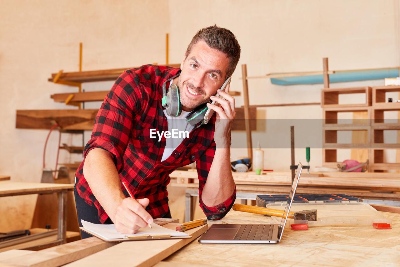 Carpenter talking mobile phone at workshop