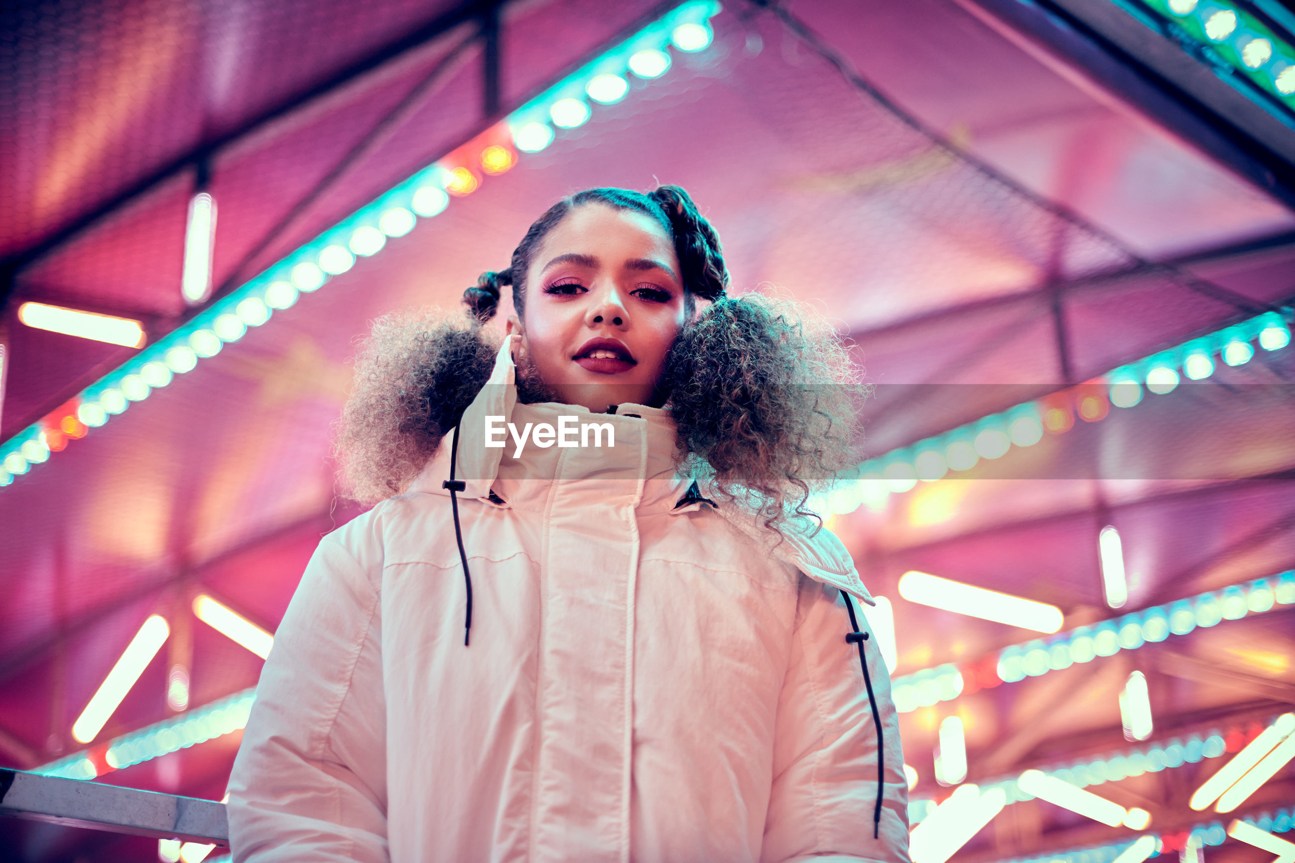 Low angle portrait of smiling young woman in amusement park at night
