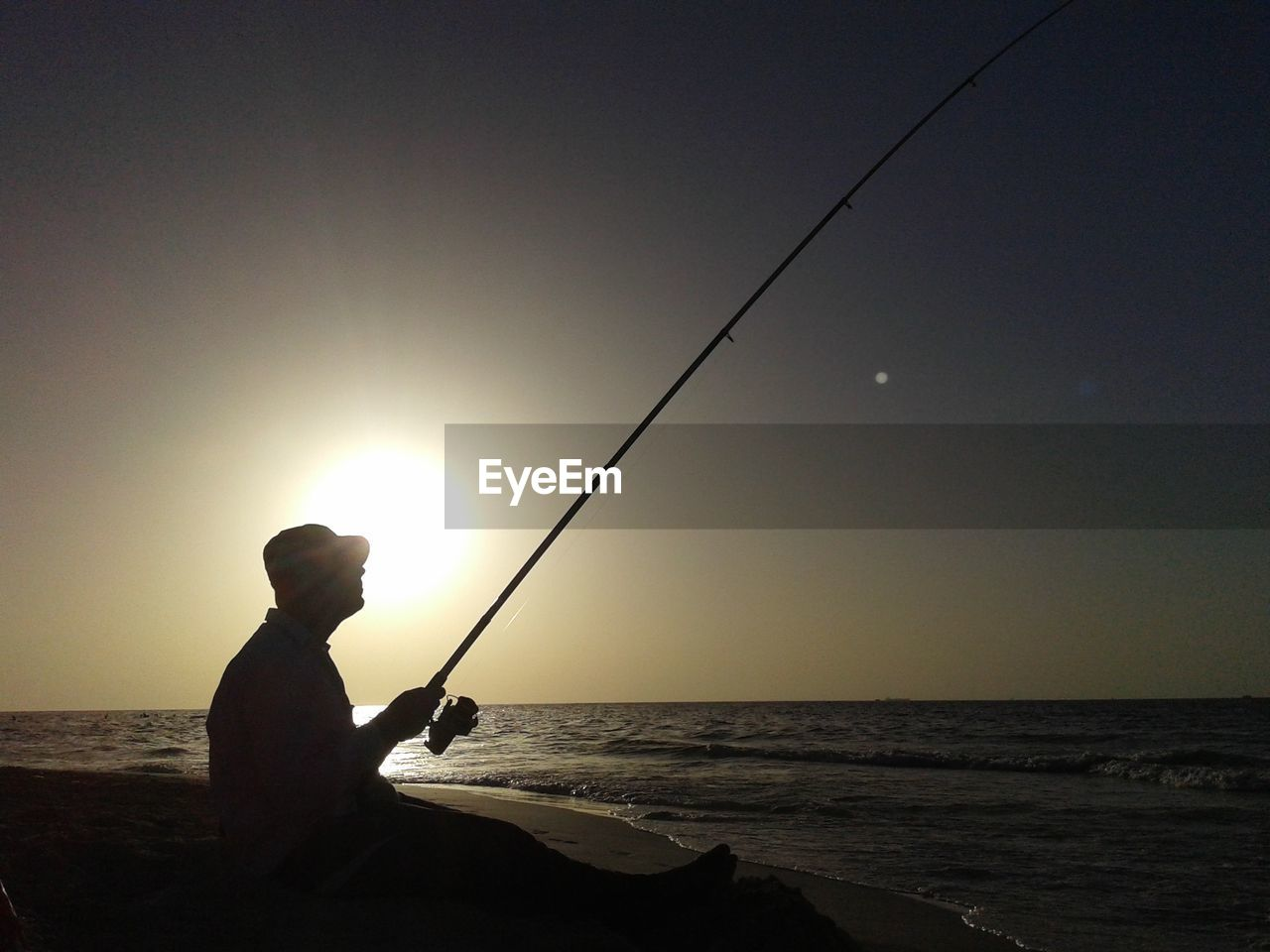 sea, fishing, fishing rod, horizon over water, fishing pole, sun, water, one person, nature, sunset, real people, silhouette, beauty in nature, tranquil scene, weekend activities, scenics, outdoors, holding, clear sky, leisure activity, sky, fishing tackle, side view, sunlight, tranquility, standing, men, full length, day, people