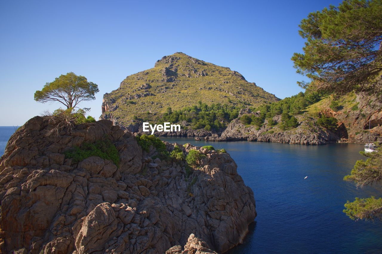Scenic View Of Rocks By Sea Against Clear Sky