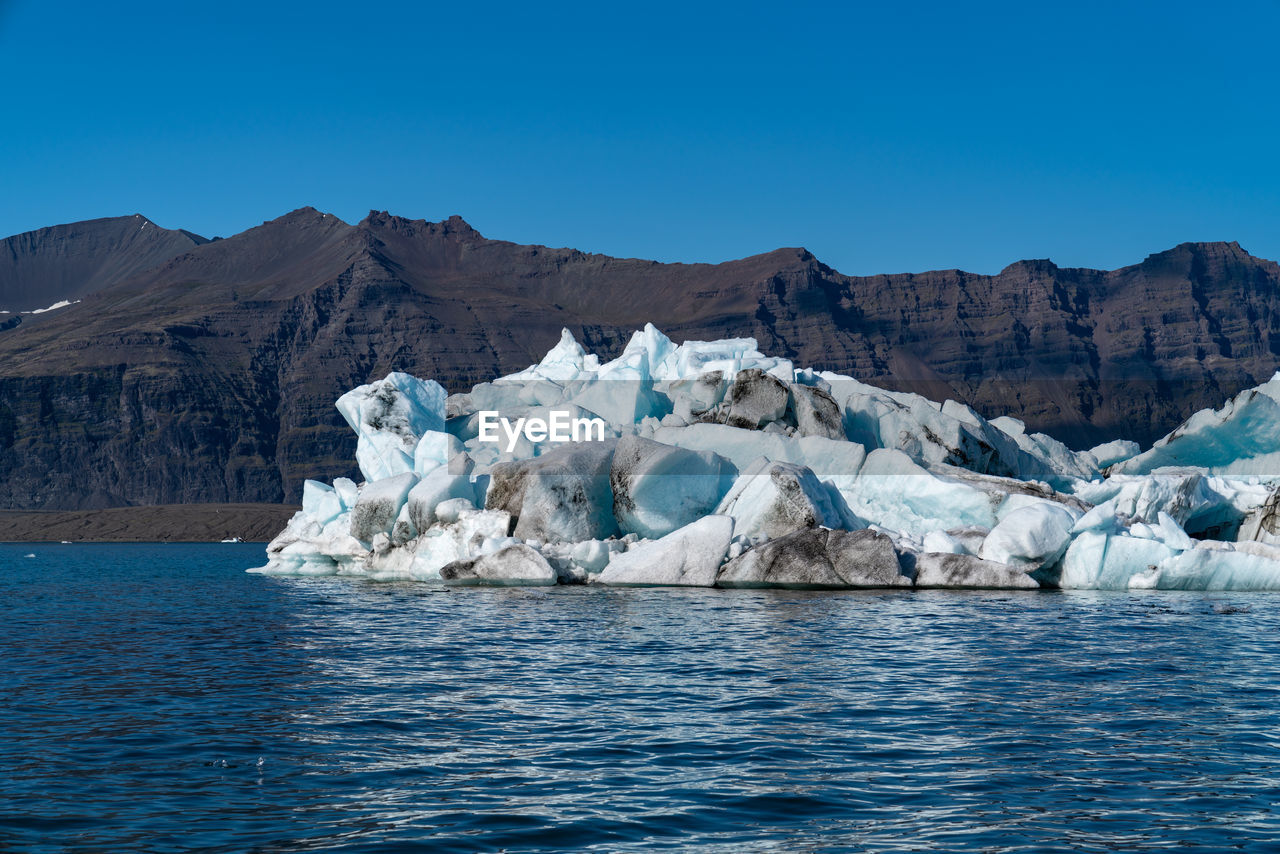 water, sky, waterfront, glacier, tranquil scene, mountain, ice, blue, beauty in nature, cold temperature, scenics - nature, tranquility, nature, landscape, clear sky, environment, idyllic, frozen, day, iceberg, no people, melting, floating on water