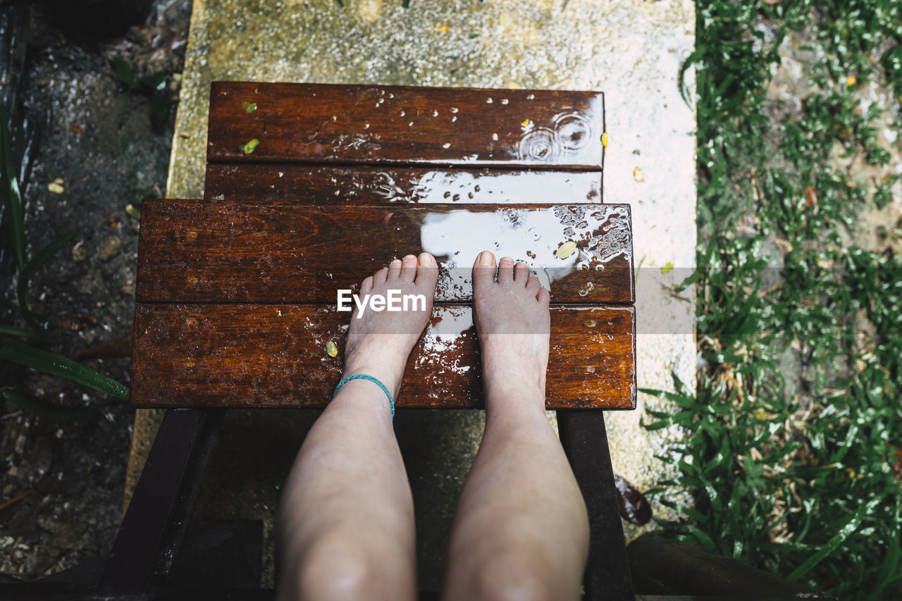 Low Section Of Woman On Wet Wooden Steps During Rainy Season