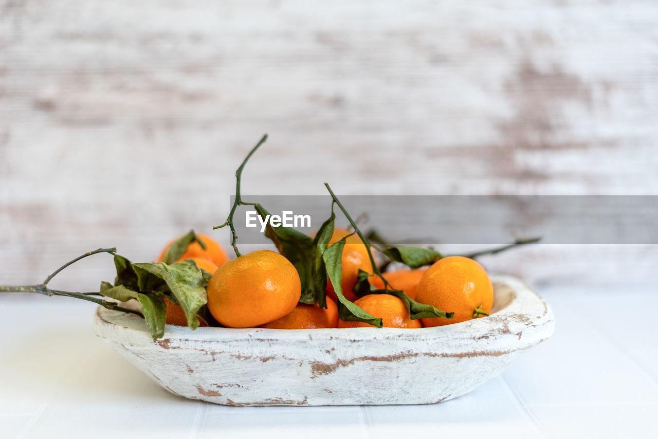 CLOSE-UP OF ORANGE FRUITS IN BOWL
