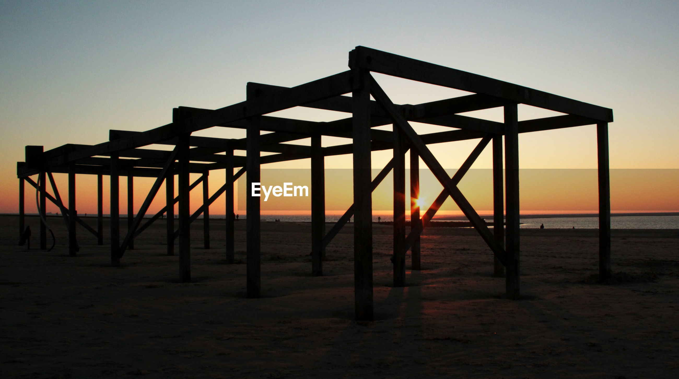 SILHOUETTE BUILT STRUCTURE ON BEACH AGAINST SKY