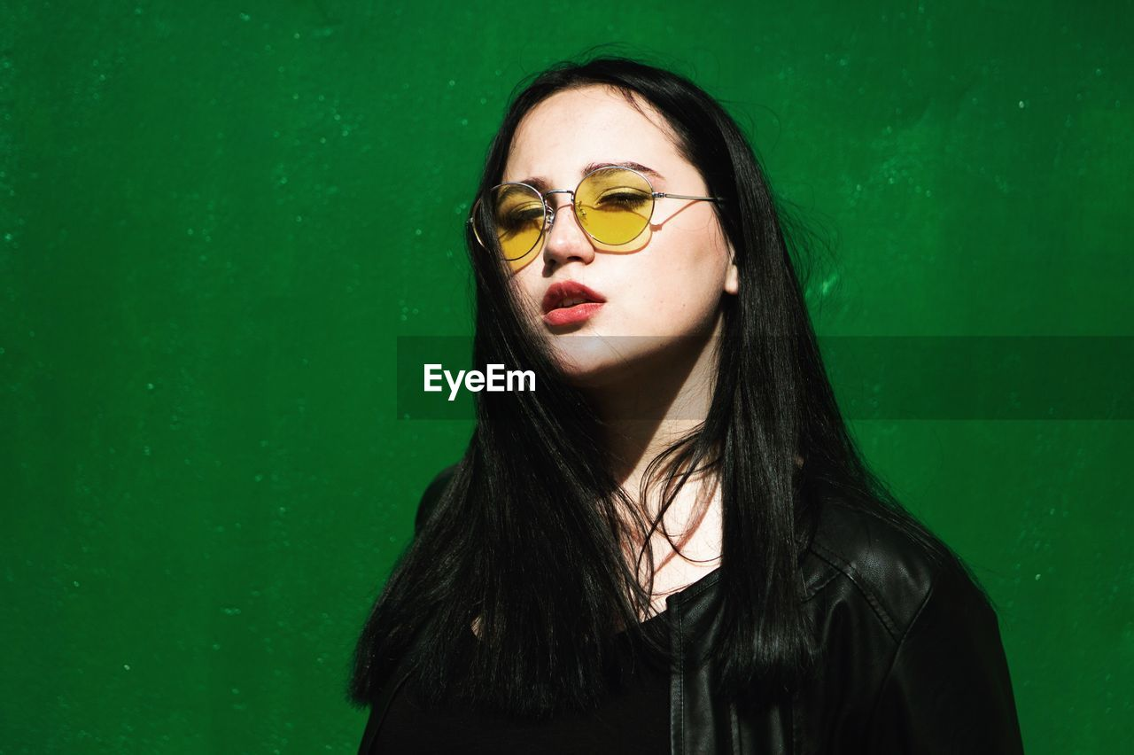 Portrait Of Young Woman Wearing Sunglasses Standing Against Green Wall