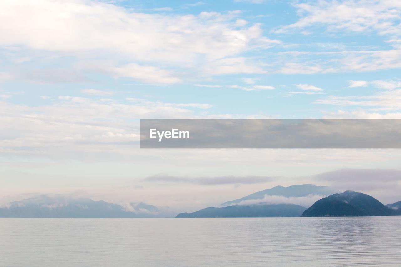 View Of Calm Sea Against Mountain Range