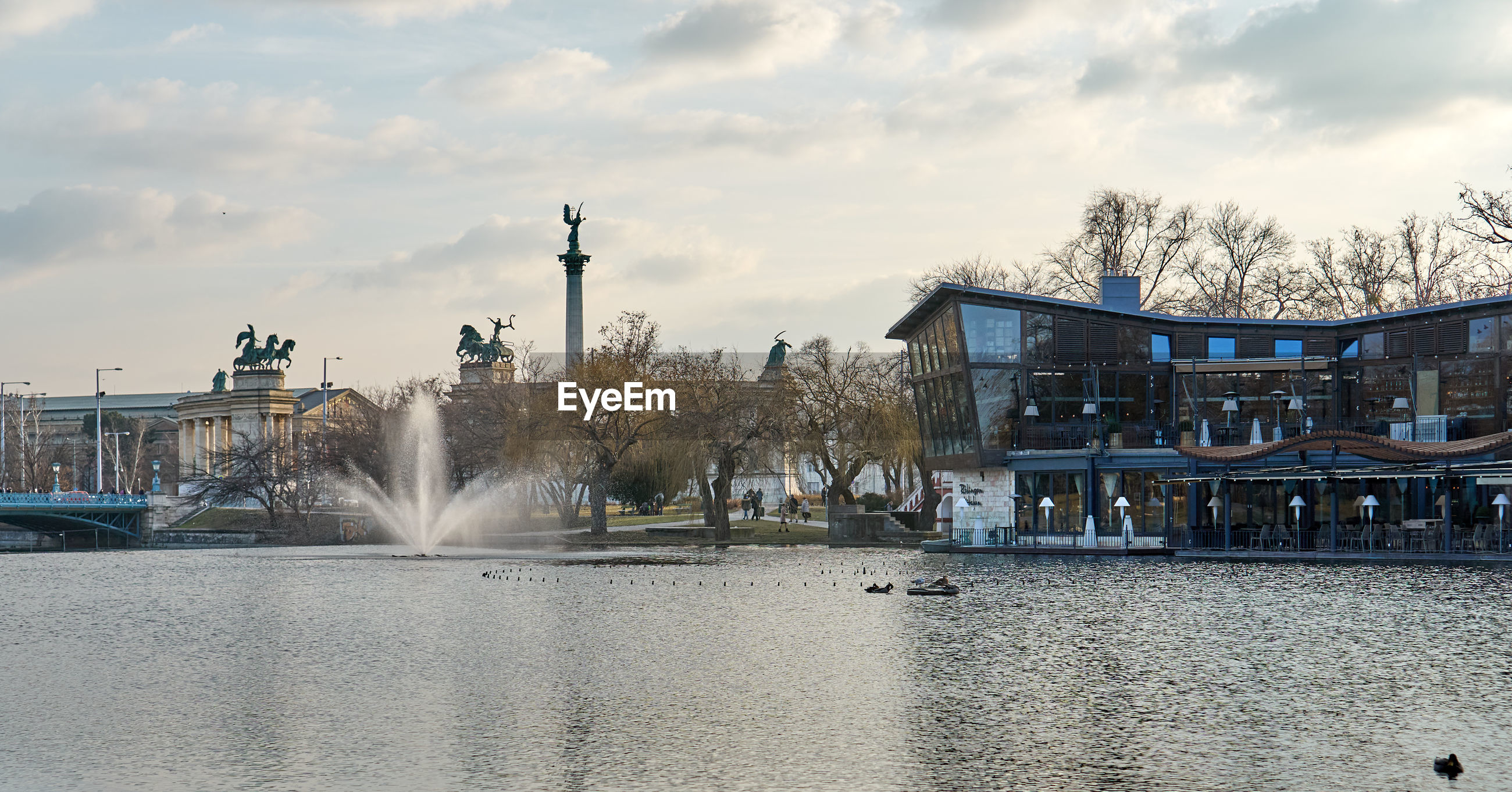 FOUNTAIN IN LAKE AGAINST BUILDINGS IN CITY