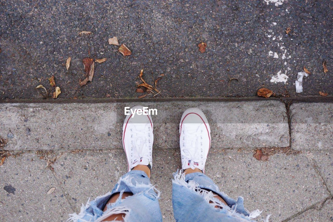 shoe, low section, body part, human body part, human leg, personal perspective, standing, one person, directly above, high angle view, day, real people, city, plant part, leaf, men, limb, unrecognizable person, footpath, human limb, outdoors, human foot, jeans, leaves, change, concrete