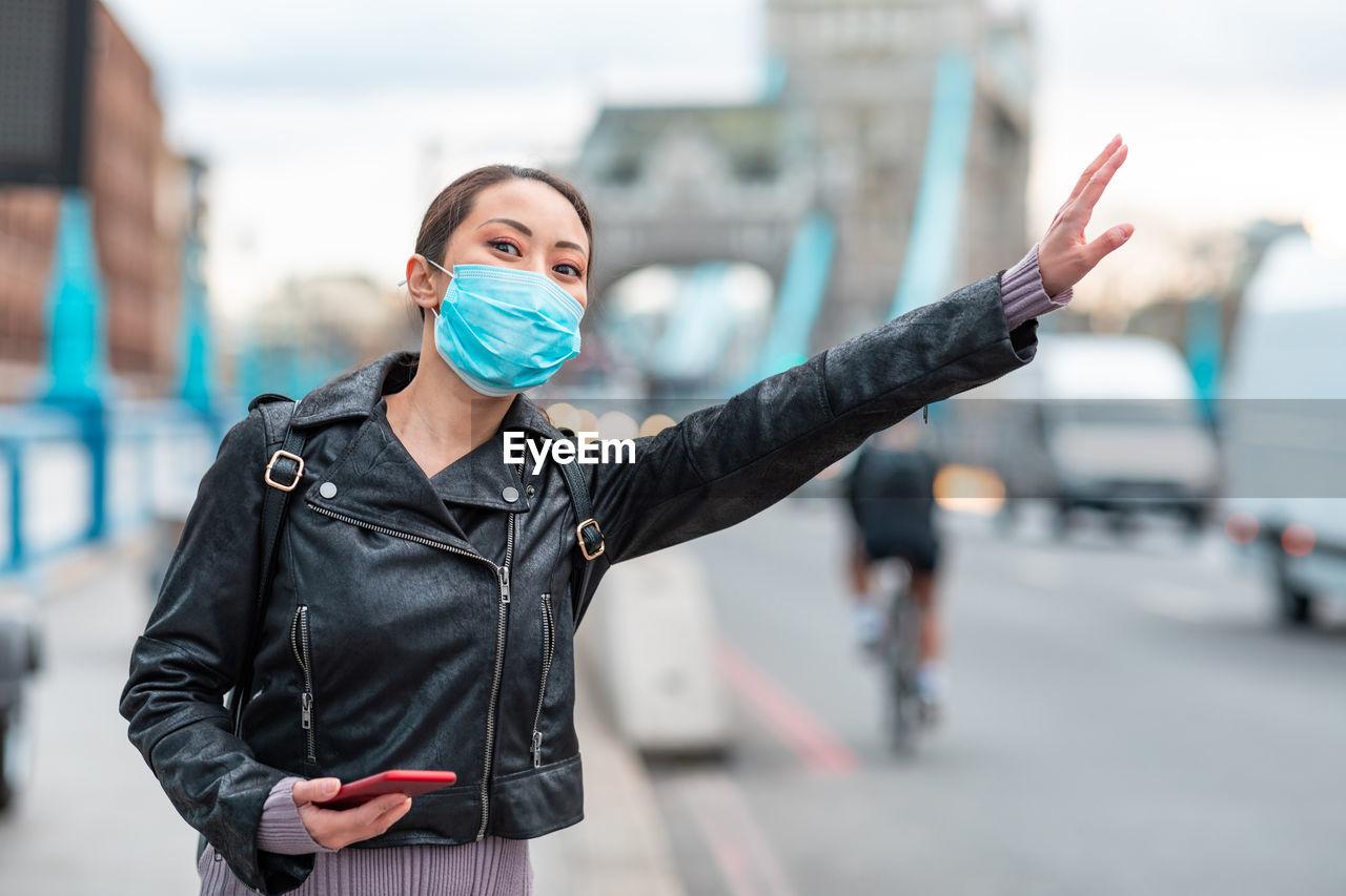 Woman wearing mask standing on street