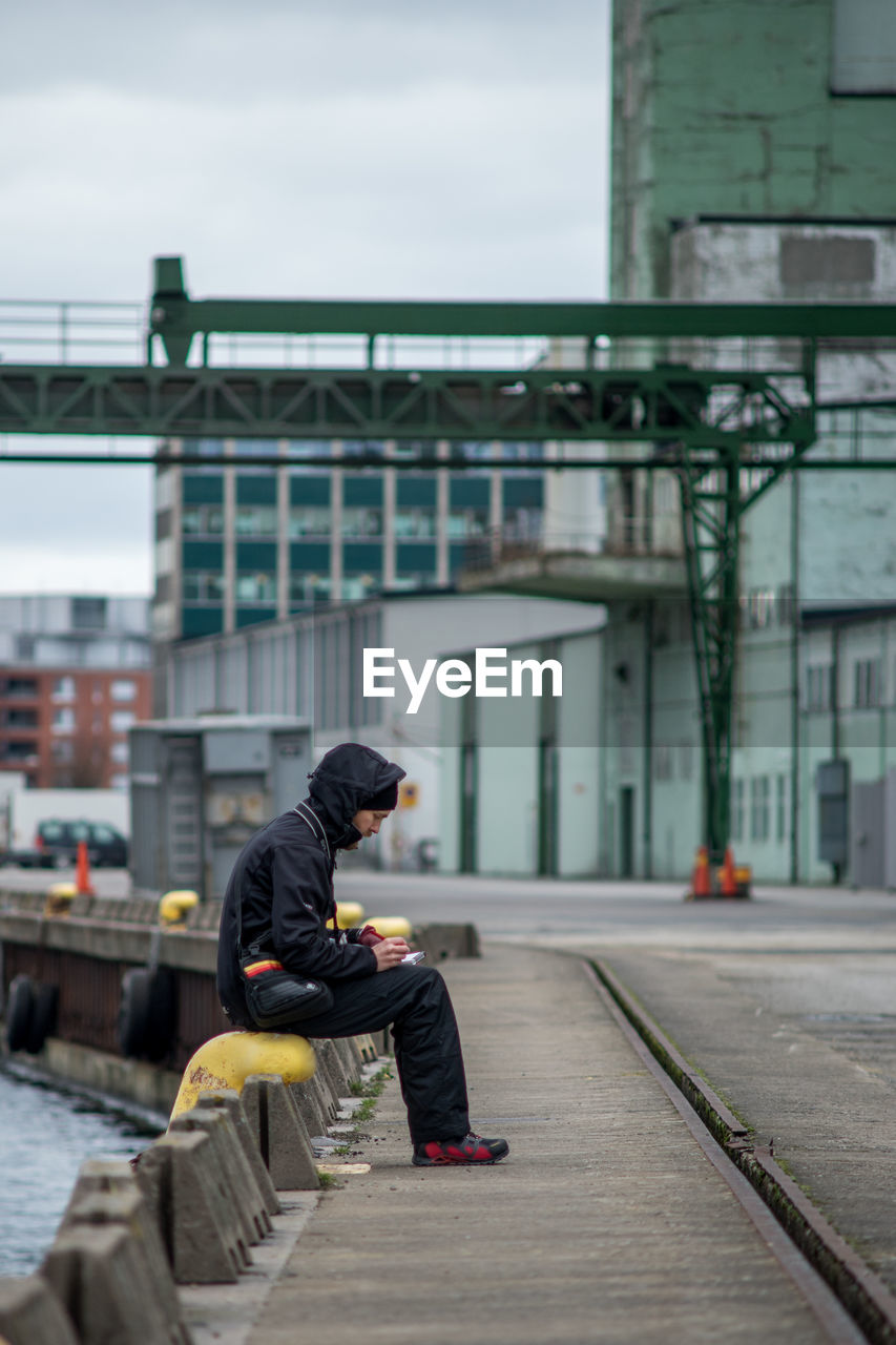 one person, real people, outdoors, day, built structure, building exterior, city, full length, men, architecture, hooded shirt, lifestyles, sky, warm clothing, people