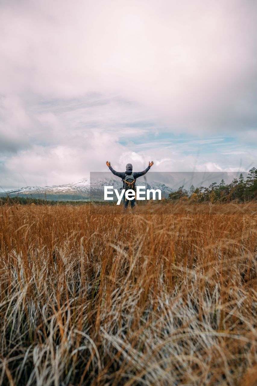Man With Arms Outstretched Standing On Field Against Sky