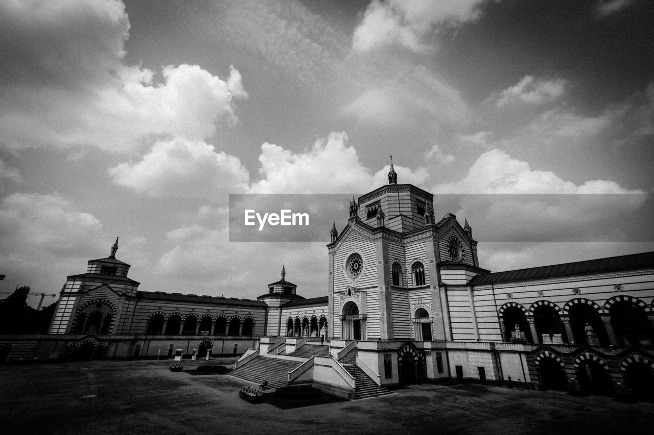 Low angle view of Famedio in Cimitero Monumentale against cloudy sky