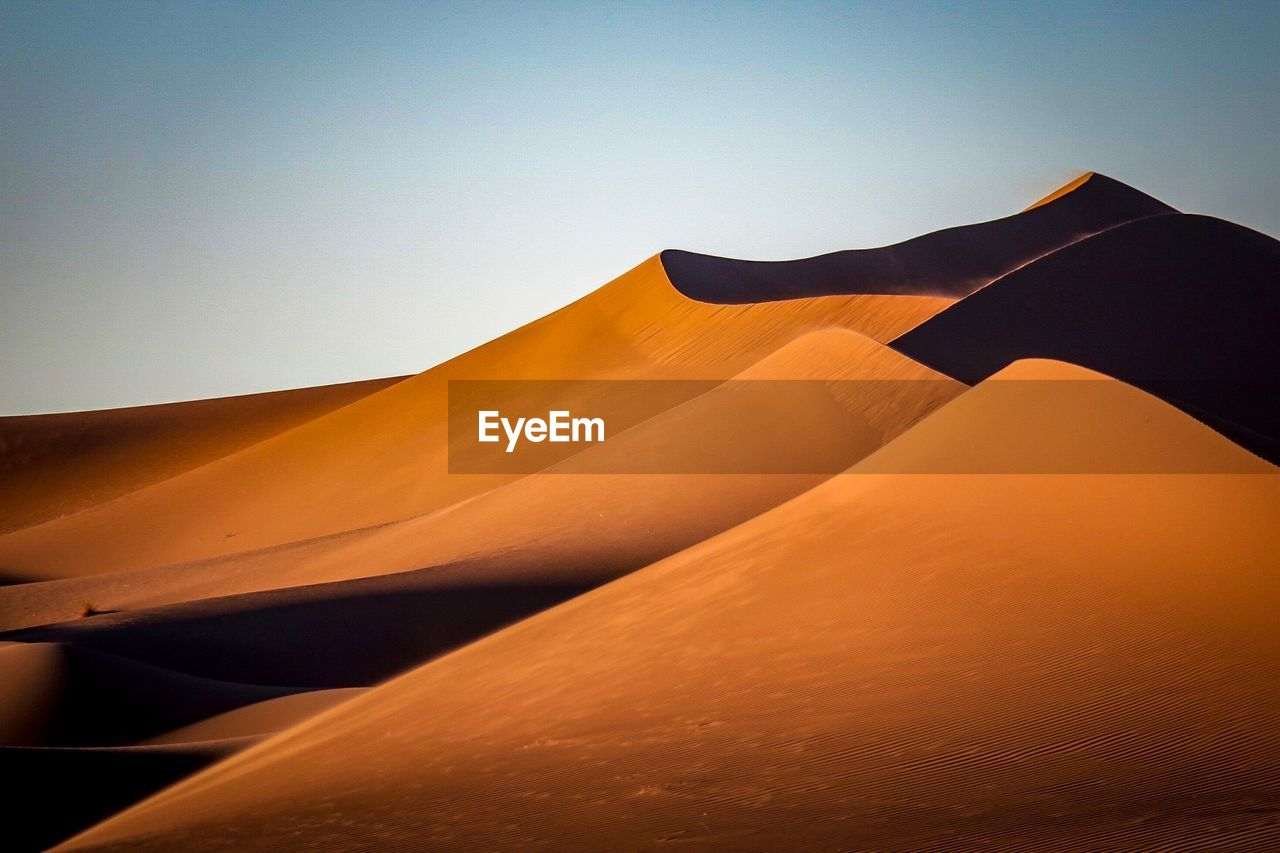 Scenic View Of Sand Dunes At Desert Against Clear Sky