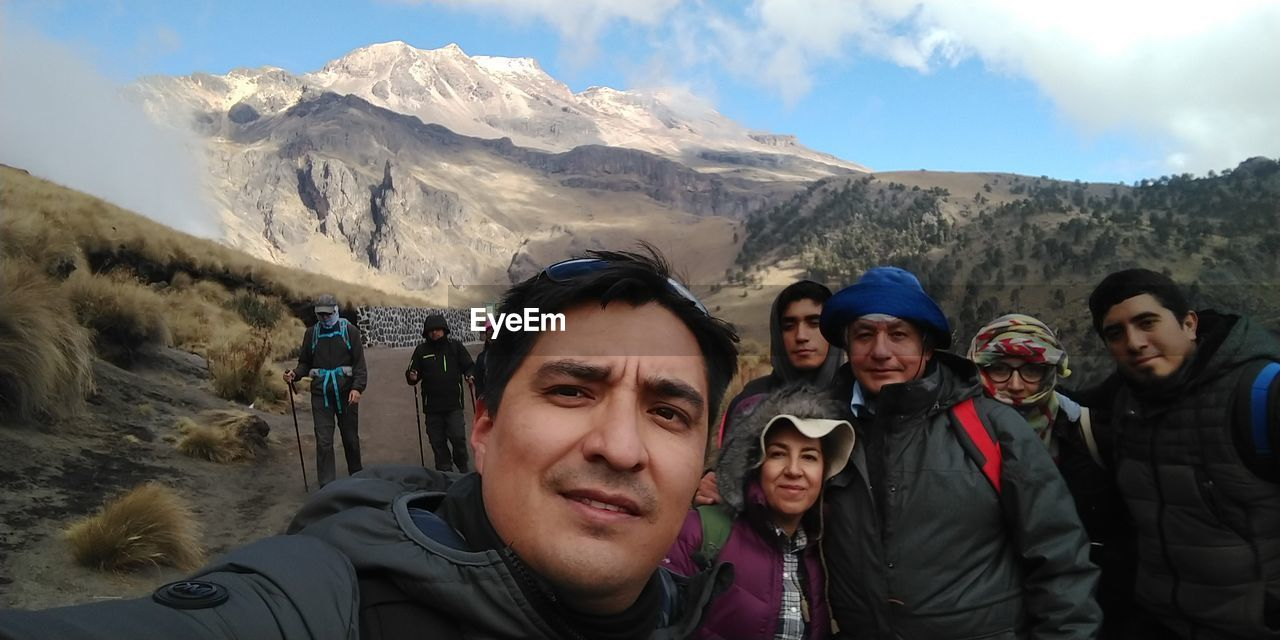 mountain, leisure activity, real people, group of people, portrait, mountain range, lifestyles, winter, scenics - nature, smiling, looking at camera, sky, adventure, people, togetherness, day, vacations, holiday, front view, warm clothing