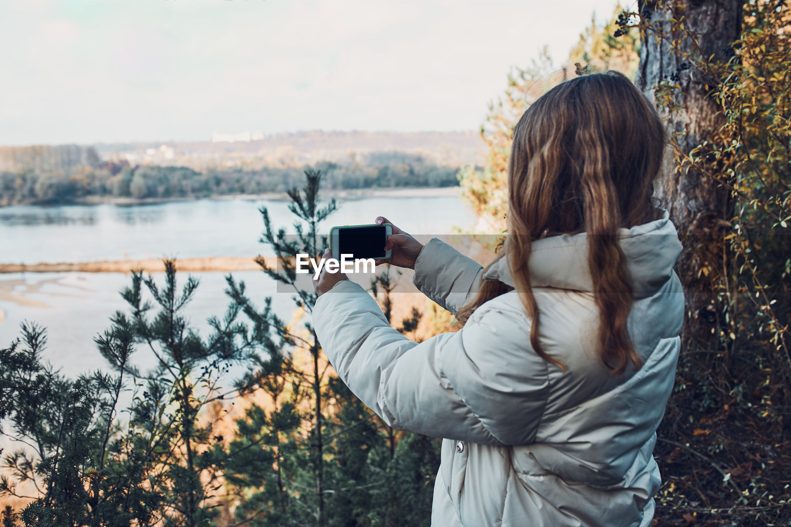 Young woman taking photos of landscape with her smartphone during trip on autumn sunny day