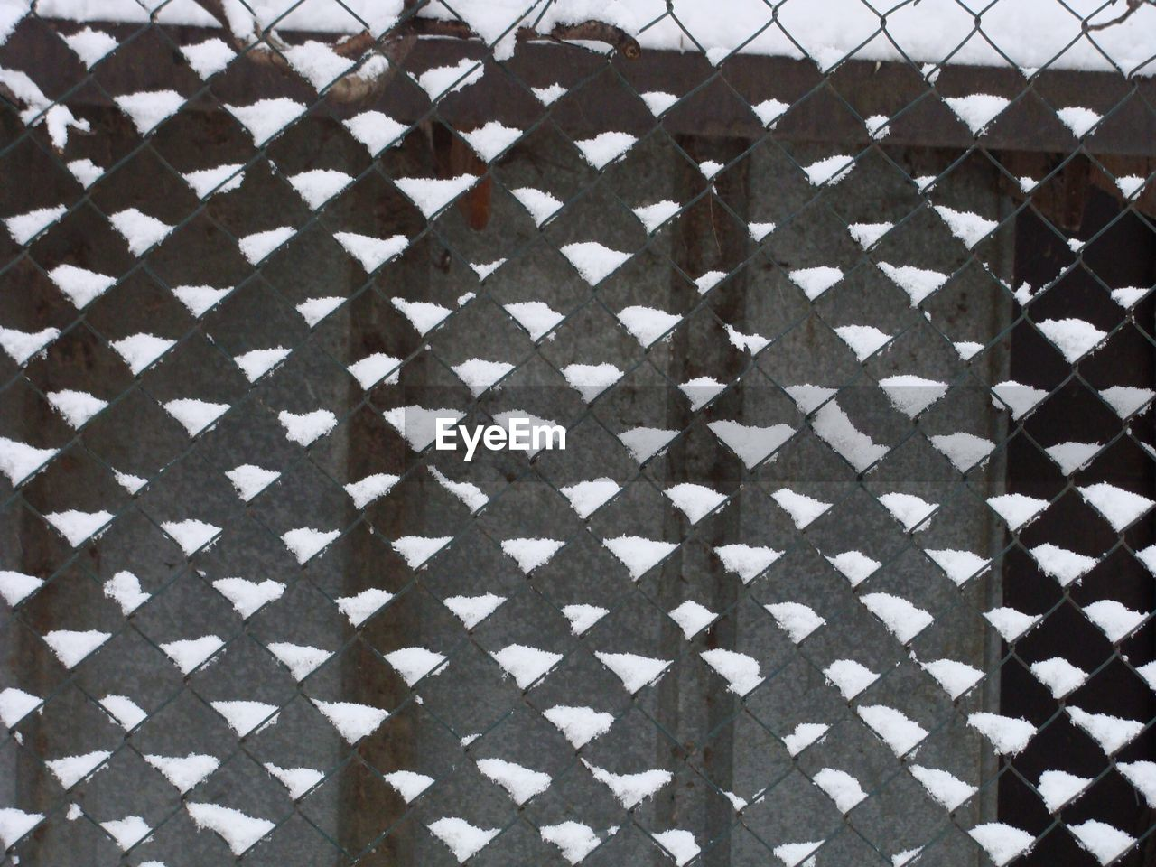 Full frame shot of snow on chainlink fence