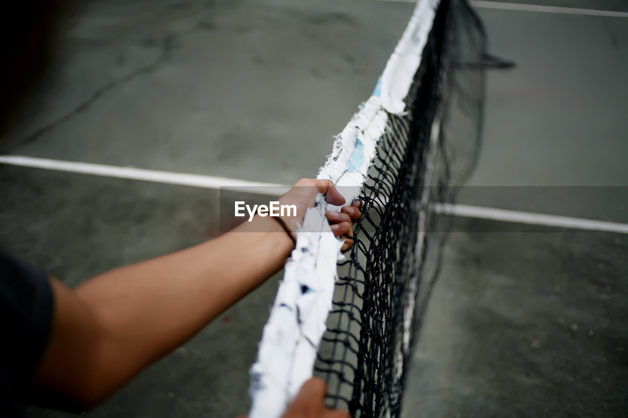 Cropped hand holding tennis net at sports court