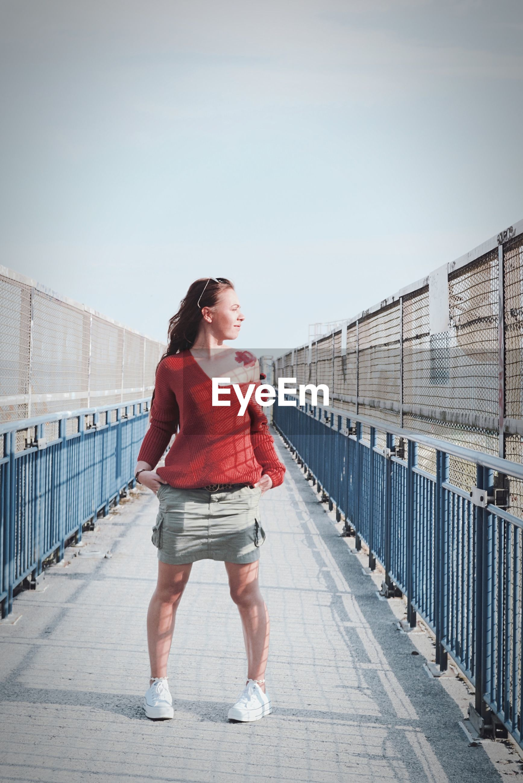 FULL LENGTH OF WOMAN STANDING BY RAILING AGAINST SKY