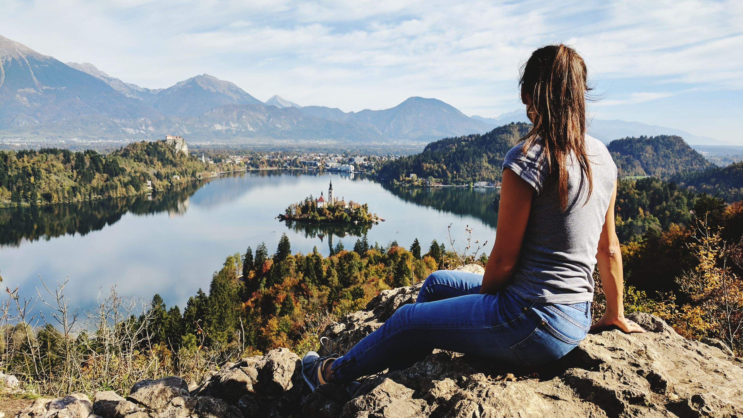 Rear view of woman sitting on rock by lake against sky