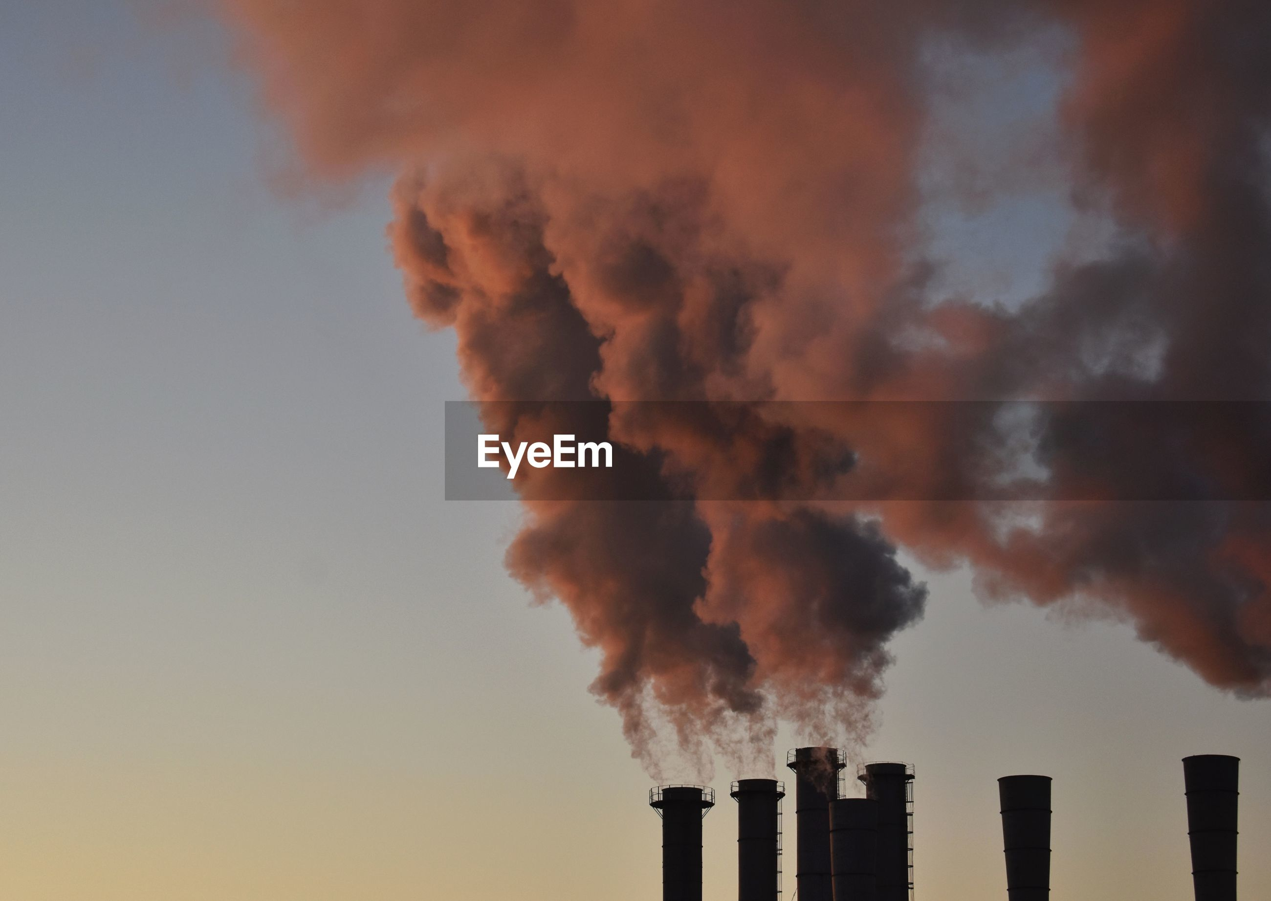 Low angle view of smoke emitting from factory against sky