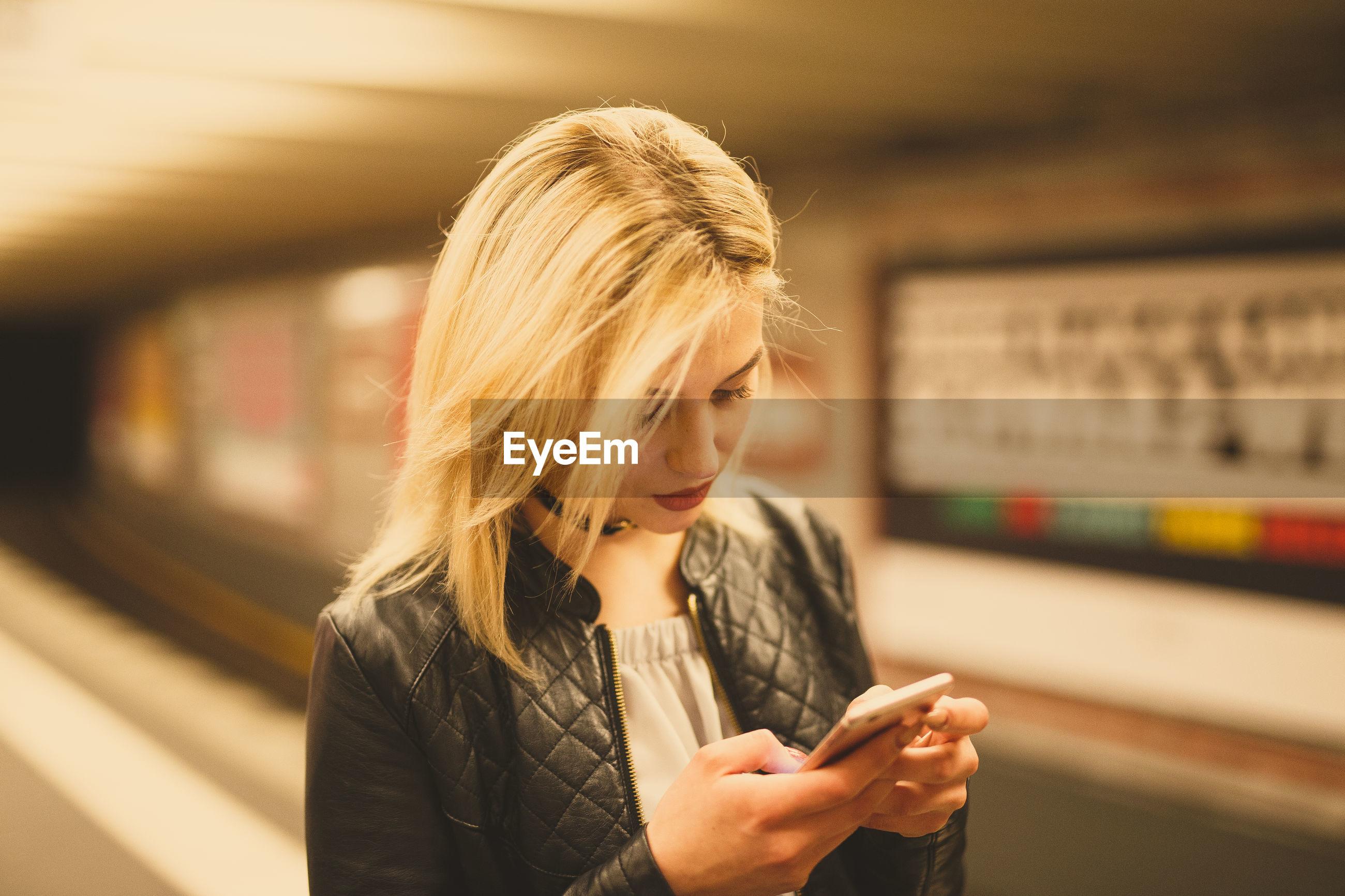 Young woman using phone at subway station