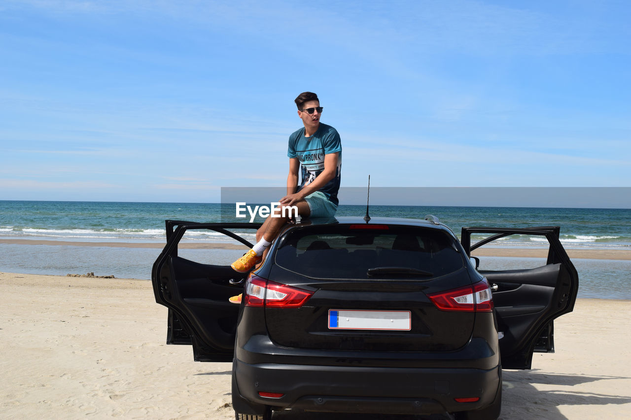 Young man sitting on car roof at beach against sky