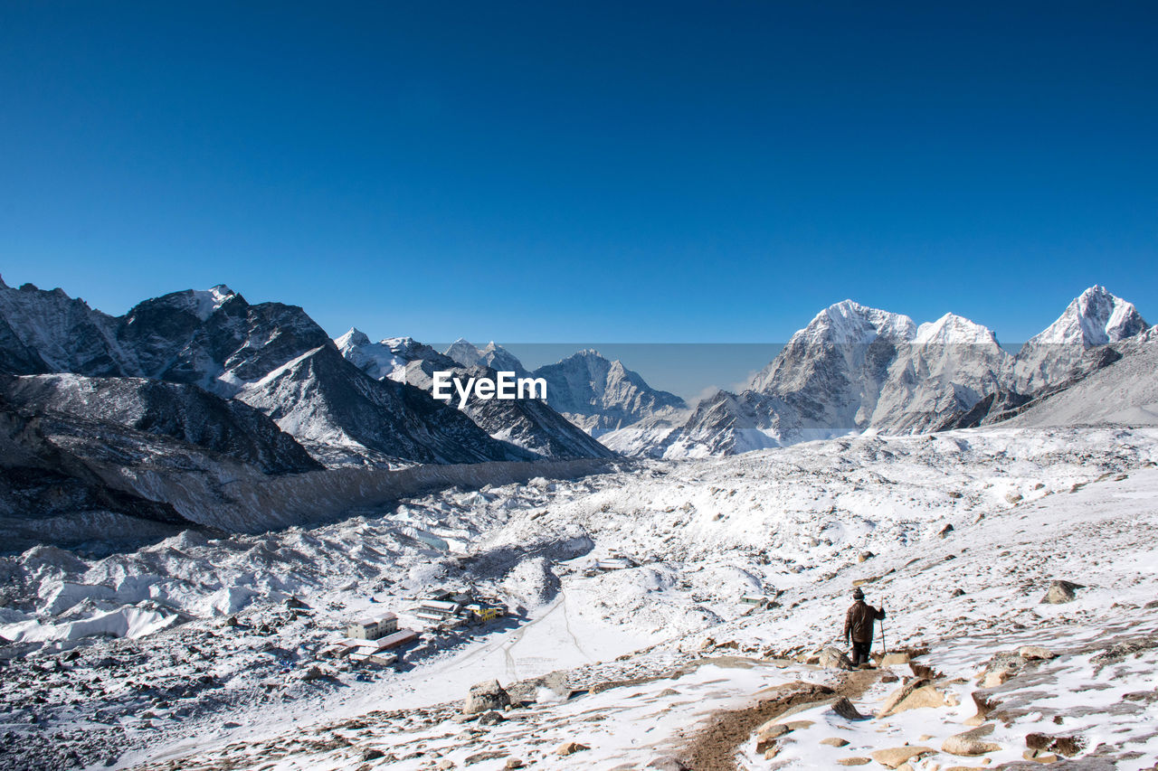 Rear View Of Man Walking On Snowcapped Mountain Against Clear Blue Sky