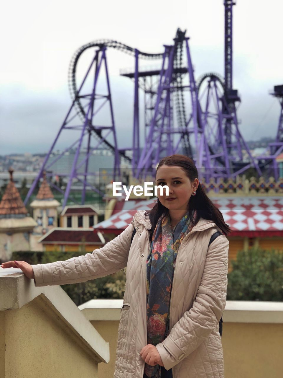 Portrait Of Woman Standing Against Rollercoaster In City