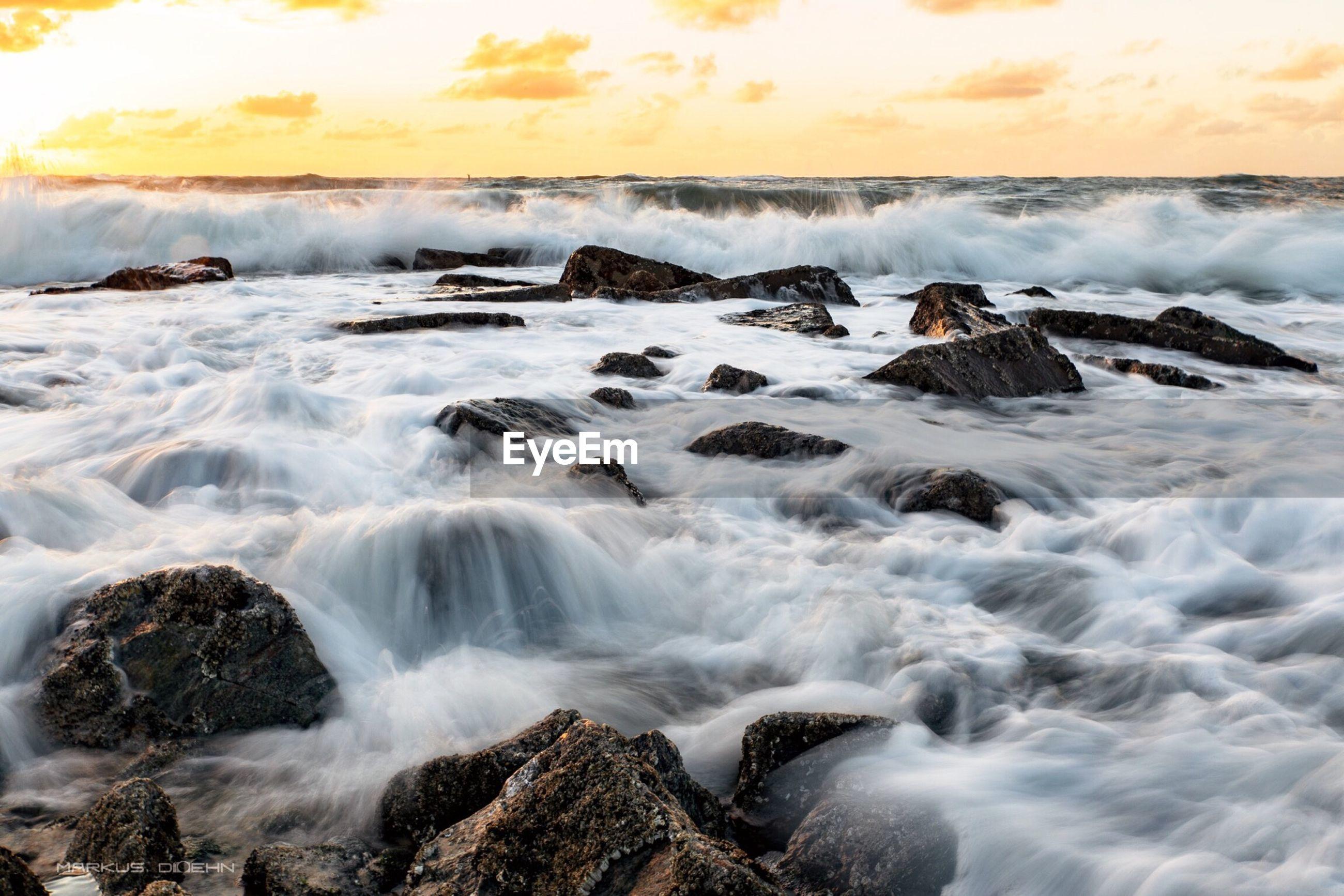Blurred motion of waves splashing on rocks at shore