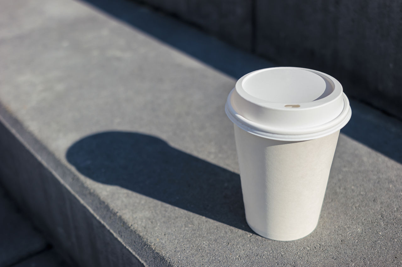 High Angle View Of White Disposable Coffee Cup On Retaining Wall