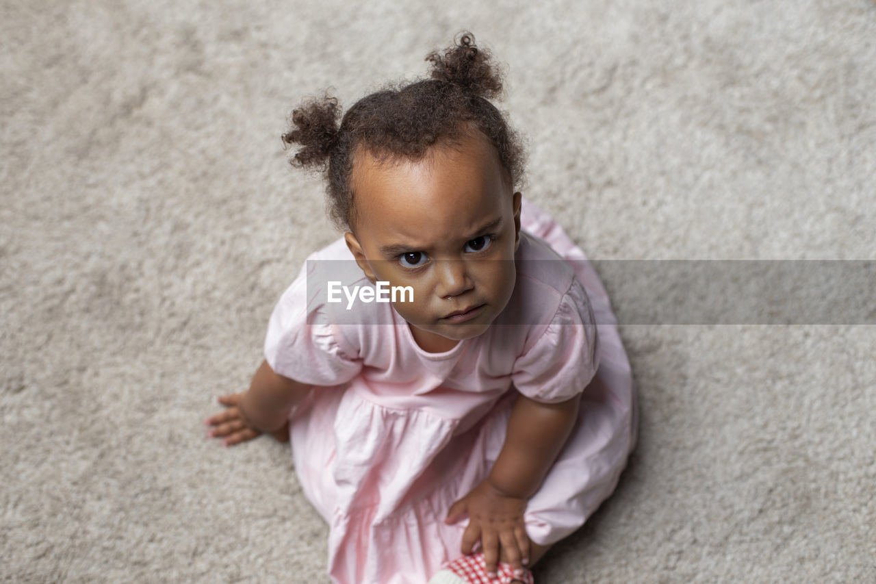 HIGH ANGLE PORTRAIT OF CUTE BABY GIRL LYING ON FLOOR