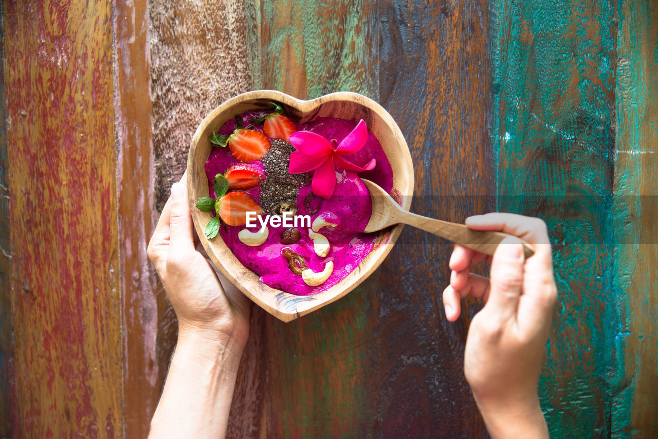 human hand, human body part, one person, food and drink, food, holding, real people, healthy eating, freshness, directly above, women, lifestyles, sweet food, pink color, close-up, indoors, multi colored, people, day, eating, one woman only, flower, adult, only women, adults only