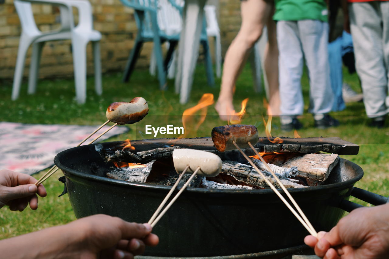 Close-Up Of People Preparing Food On Barbecue Grill