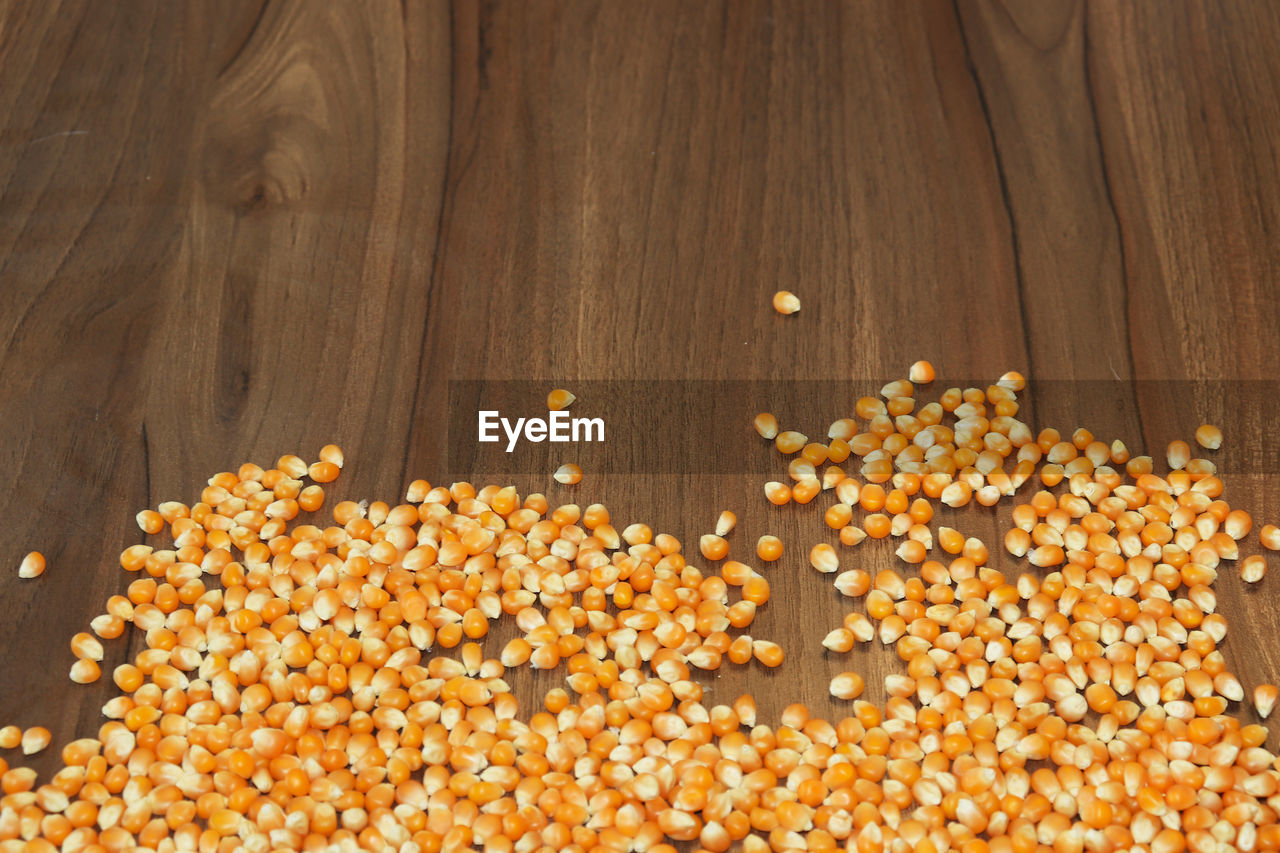 food and drink, food, corn, freshness, healthy eating, wellbeing, cereal plant, high angle view, no people, vegetable, agriculture, indoors, close-up, still life, large group of objects, table, seed, wood - material, abundance, sweetcorn