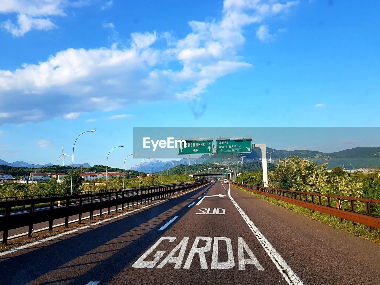 ROAD SIGN ON BRIDGE AGAINST SKY AT DUSK
