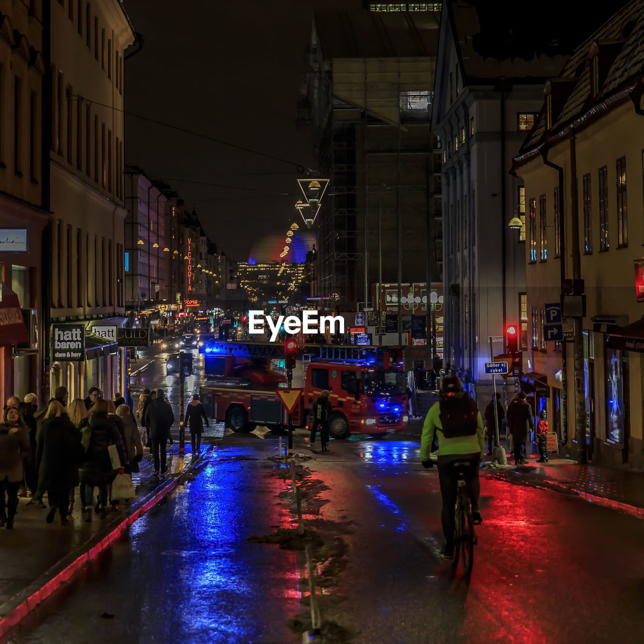 architecture, city, illuminated, night, building exterior, group of people, built structure, real people, street, transportation, city life, mode of transportation, lifestyles, men, large group of people, crowd, women, city street, road, outdoors