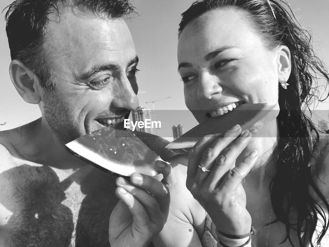 Smiling couple eating watermelon