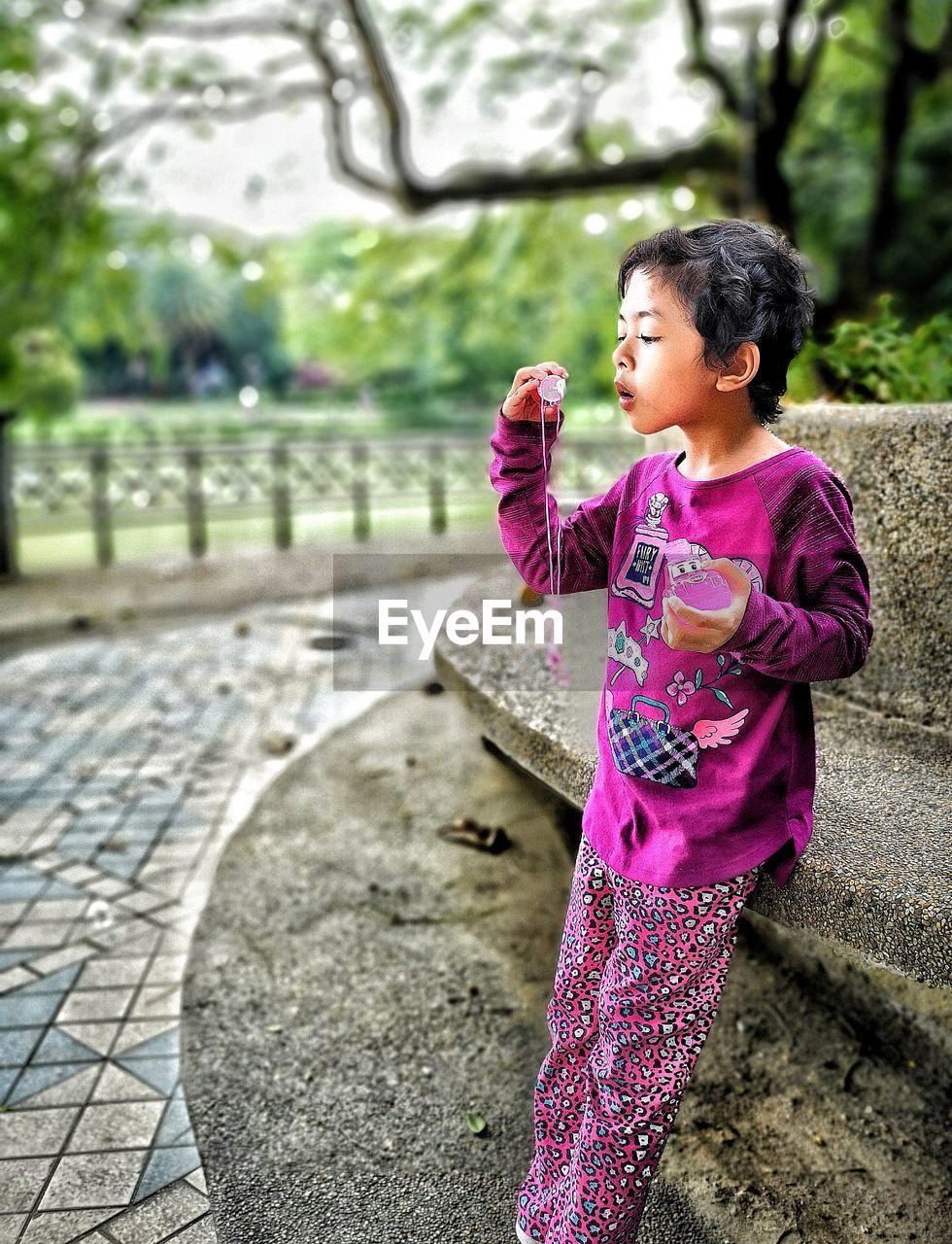 childhood, one person, females, child, girls, women, real people, leisure activity, lifestyles, casual clothing, day, focus on foreground, full length, side view, three quarter length, standing, pink color, looking, innocence, outdoors, purple, hairstyle