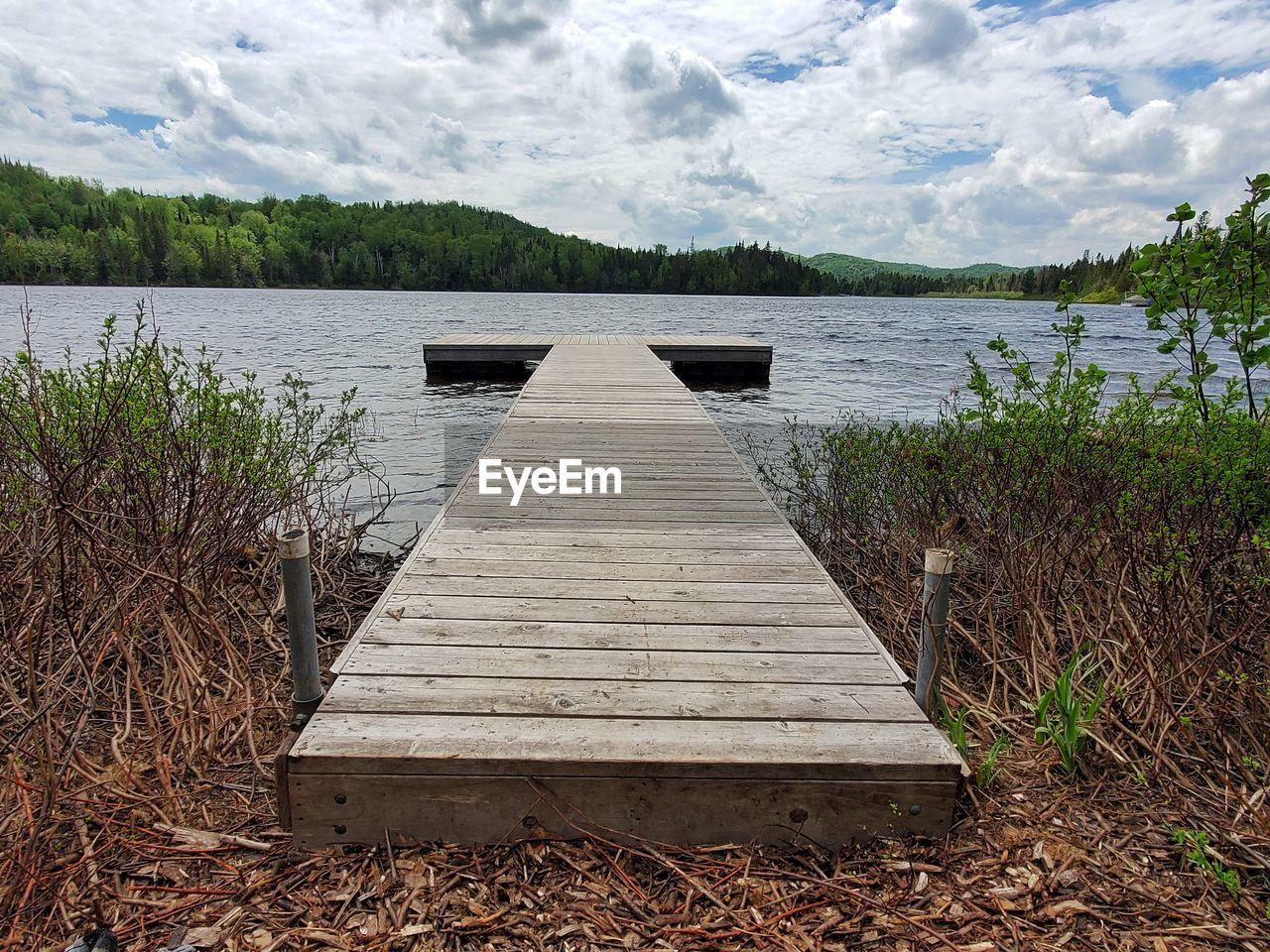 EMPTY PIER OVER LAKE AGAINST SKY