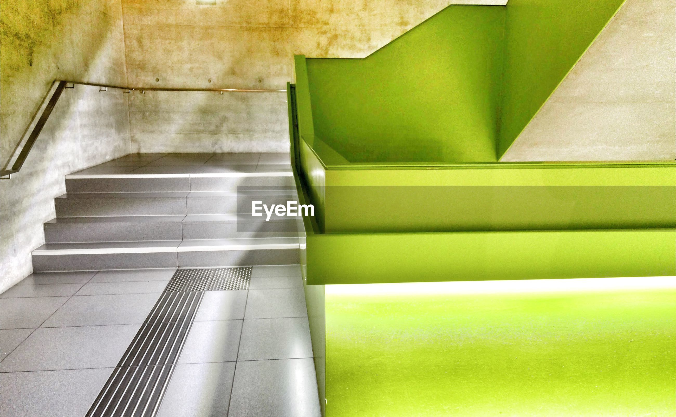 indoors, green color, absence, empty, built structure, architecture, wall - building feature, no people, steps, in a row, wall, steps and staircases, staircase, seat, pattern, sunlight, high angle view, day, modern, chair