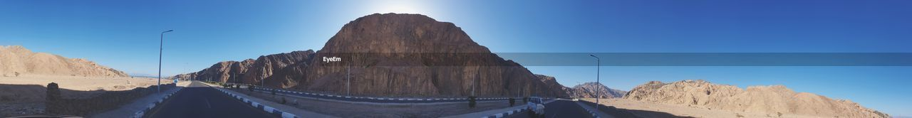 sky, mountain, rock formation, nature, sunlight, rock, blue, scenics - nature, day, beauty in nature, rock - object, panoramic, mountain range, clear sky, solid, tranquility, travel destinations, tranquil scene, no people, travel, outdoors, formation