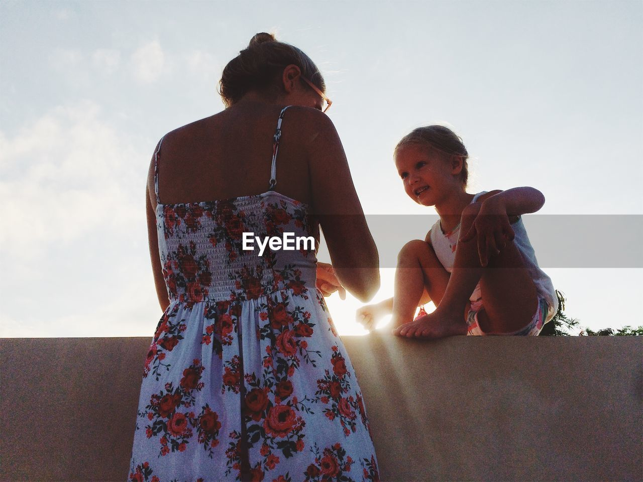 Low Angle View Of Mother And Daughter Against Sky