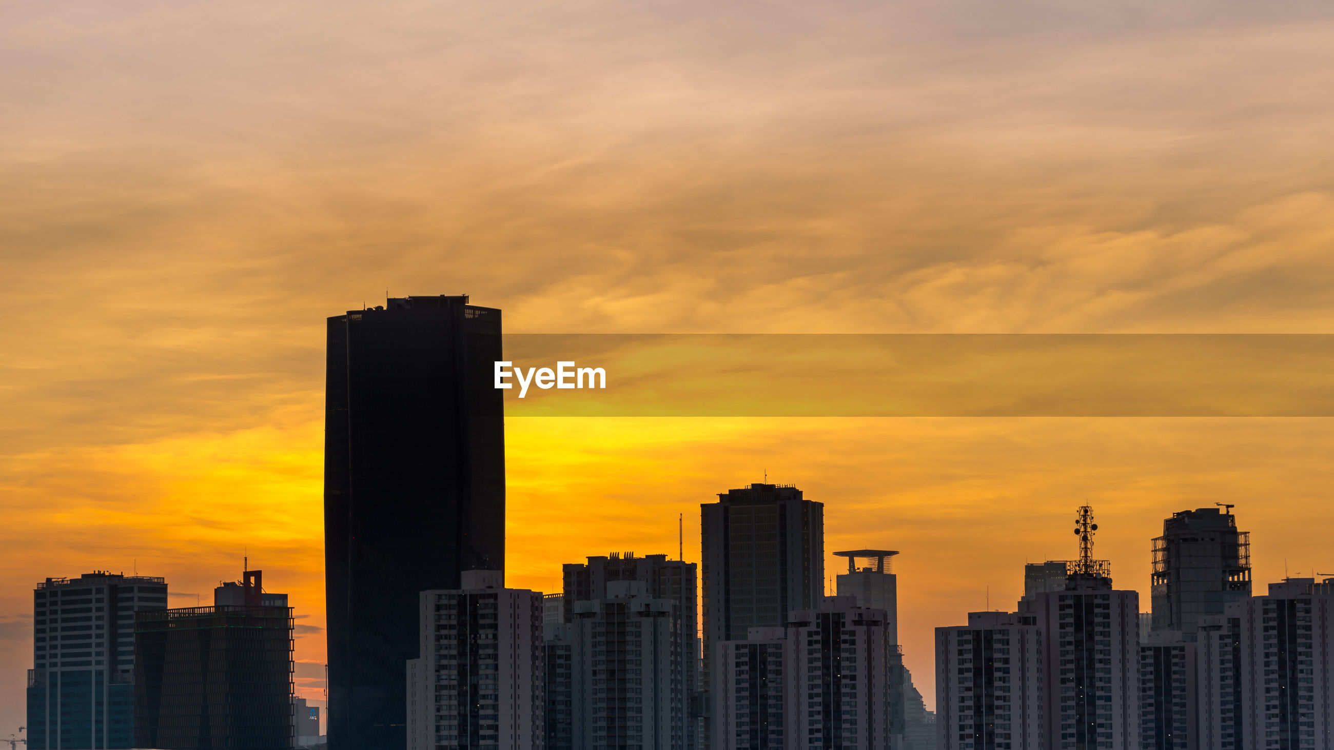 High section of skyscrapers against sunset sky