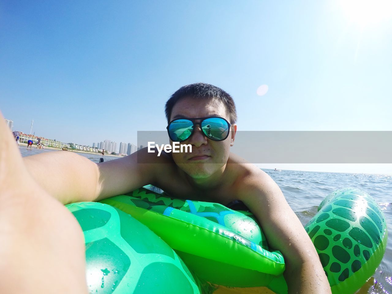 Portrait of shirtless man wearing sunglasses while lying on inflatable ring over sea