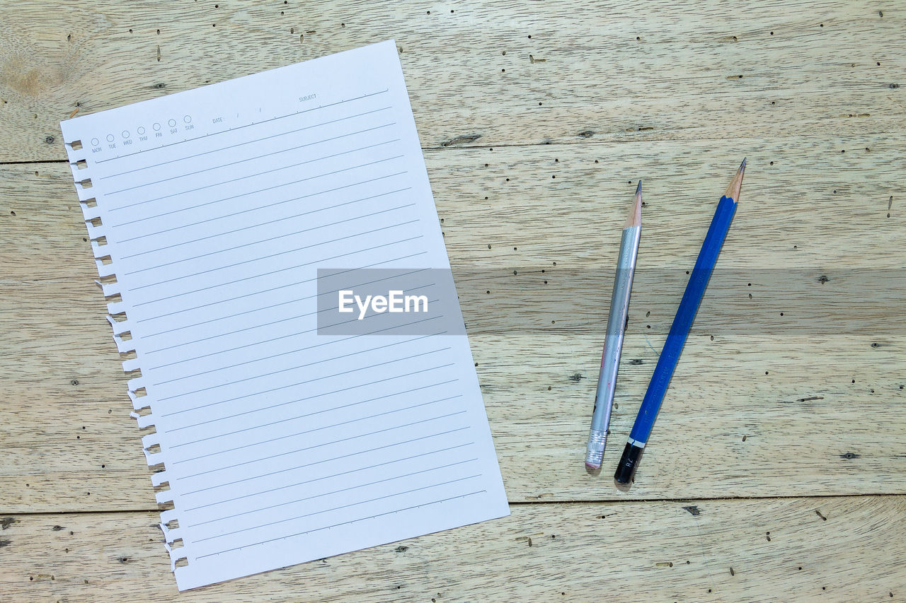 table, pen, paper, education, pencil, note pad, writing instrument, high angle view, no people, still life, indoors, book, blank, publication, blue, close-up, two objects, wood - material, open, white color