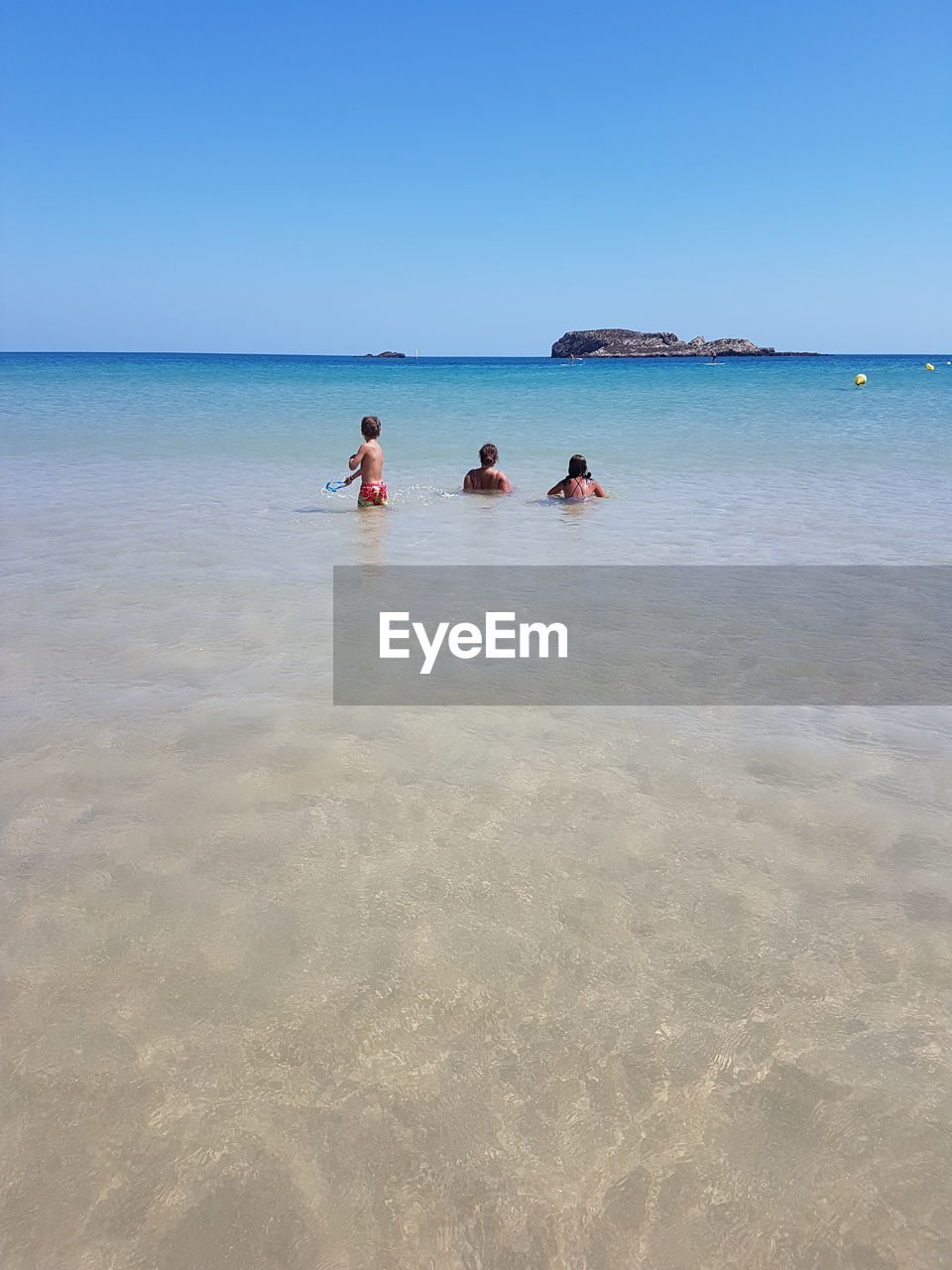 PEOPLE ENJOYING AT BEACH AGAINST CLEAR SKY